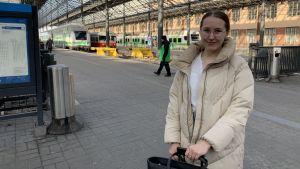 Siiri Koivisto står på perrongen på Helsingfors järnvägsstation. Hon har på sig en ljus, lång rock, och under det en vit skjorta. Hon tittar in i kameran och ler. Bakom henne skymtar ett tåg.