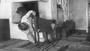 """En man leker leken """"krypa runt stolen"""", där han ska vrida sig runt stolen utan att vidröra golvet. Bilden är tagen 1936 i Strömfors, Kungsböle."""