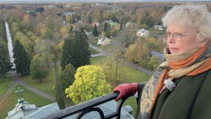 En kvinna med halsduk står vid ett räcke i ett torn och blickar ut över Korsholms skogar