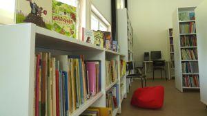 En hylla med barnböcker, andra hyllor med böcker i ett bibliotek, en röd säckdyna på golvet, i bakgrunden en dator på ett bord.