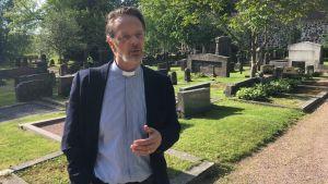 Kyrkoherde med prästkrage på en begravningsplats.