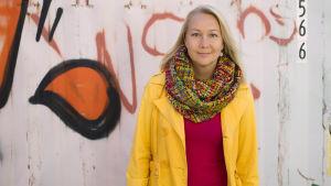 Mia Rahunen framför en containervägg.