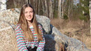 Bianca sitter på en sten och ler in i kameran.