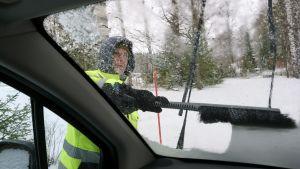 En man sopar en bilruta ren från snö i maj
