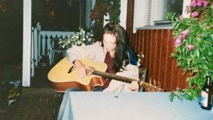 Sofie Stara som tonåring spelar gitarr på terrassen.