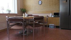 Ett runt bord med stolar i ett litet kontor tänkt för distansarbete. Gröna växter vid fönstret och en klocka på väggen.