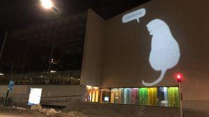 En bild av en katt som ljuskonstverk på Åbo huvudbiblioteks vägg.