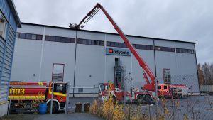 Nostoauton kori teollisuushallin katolla, ympärillä paloautoja