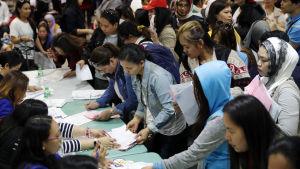 Filippinska hushållsarbetare sitter på flygplatsen i Manilla efter att ha hämtats tillbaka från Kuwait. Bilden är tagen i februari 2018.