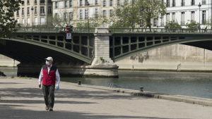 mies kävelee sillan edessä maski päällä