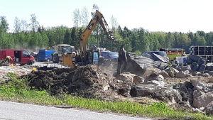 En grävmaskinist lyfter mattor som används vid sprängning på Ingåport.