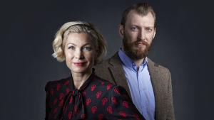 Porträttbild av Anna-Karin Wyndhamn och Ivar Arpi som poserar och tittar in i kameran, i en mörklagd studio.
