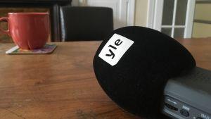 En diktafon med Yles logo ligger på ett bord. En stor tekopp i bakgrunden.