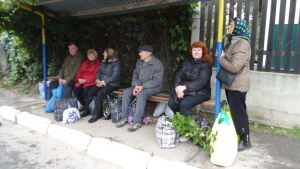 Irina väntar på bussen på en hållplats nära soptippen