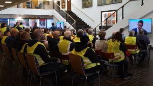 Människor i gula reflexvästar följer med fusionsdebatt i Korsholm.