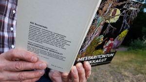 Mies lukee Mestaritontun seikkalut -kirjaa puistossa