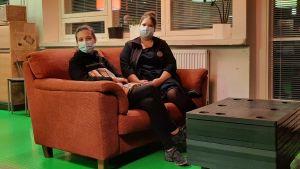 Två kvinnor med munskydd sitter i en soffa.
