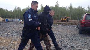 Aktivist förs bort av polis.