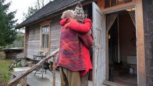 Petra och Charlie kramar varandra ute på trappan till huset de byggt.