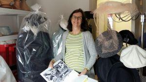 Textilforskare Helena Sandström-Snickars på Österbottens museum planerar en sommarutställning med Elin Nelins hatt, studentmössa och dräkter. På bilden i Helenas händer syns Elin iklädd en av dräkterna och studentmössan i samband med en klassträff.