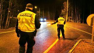 Två poliser visar åt en bil att den ska stanna.