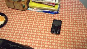 Kännykkä pöydän päällä.