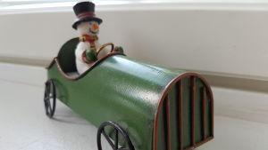 lumiukko ajaa puisella leikkiautolla