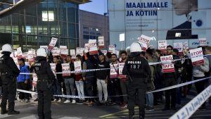 Demonstranter vid helsingfors-Vanda flygplats övervakas av poliser.