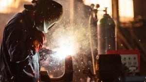 Person som utför metallarbete med visir, gnistor i mörk omgivning.