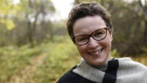 Kvinna med glasögon ler mot kameran