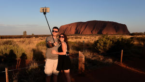 Två turister tar en selfie framför Uluru.