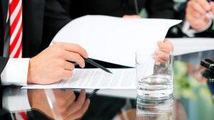 Affärsman läser genom ett avtal.
