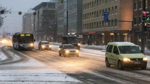 Autoja mannerheimintiellä lumisateessa aamuhämärässä