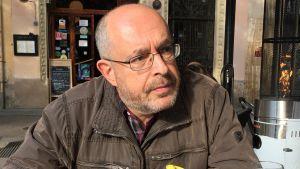 Journalisten Jaume Martinez Hernandez sitter på en uteservering med händerna knäppta.
