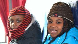 Två barn som åker buss, en flicka och en pojke.