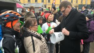 Matti Vanhanen signerar ämbar i folkmassan på Narinken.