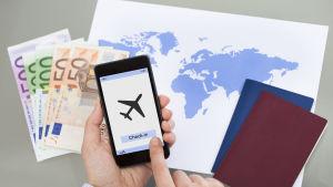En hand håller i en mobiltelefon och ska checka in på ett flygplan. På bordet framför ligger pengar, en världskarta och två pass.