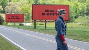 skådespelare Frances McDormand framför en tre raklamskyltar