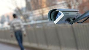Övervakningskamera och skugga av en person i bakgrunden.