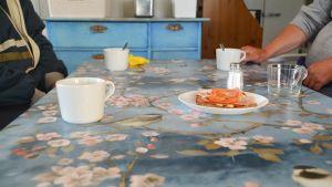Matbord, blå duk, kaffekoppar och smörgåsar, vid bordskanten männens armar..