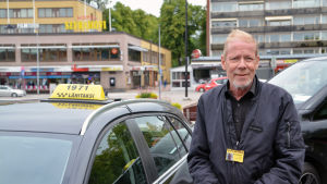 Hannu Polttila står vid taxibil.