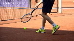 Benen på en tennisspelare som håller i ett tennisracket.