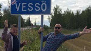 Micke Björklund och Matias Jungar vid en vägskylt som det står Vessö på.