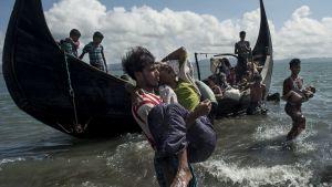 Arkivbild på en bangladeshisk man som hjälper flyende rohingyer att ta sig i land på bangladeshisk mark vid floden Naf den 30 september 2017.