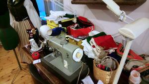 En symaskin och ett stort antal tygbitar på ett bord.