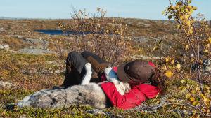 Kiharahiuksinen, lippalakkiin ja vaellusvarustukseen pukeutunut nainen makaa maassa tunturimaisemassa ja halaa valkeanharmaata koiraa.