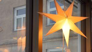 En bild på en julstjärna som hänger i ett fönster