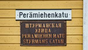 Keltaisessa puutalossa katukyltti jossa teksti Perämiehenkatu, alla kyltti jossa venäjänkielistä tekstiä