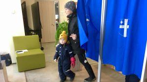 Mor och son lämnar båset i vallokalen i Muraste i Keila kommun strax utanför Tallinn.
