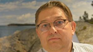 Sami Heinonen, en man med glasögon och randig skjorta.